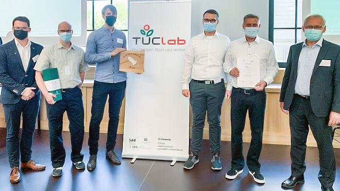 """Das Fotos zeigt sechs männliche Personen mit Corona-Maske links und rechst von einem Rollup mit der Aufschrift """"TUClab"""". Drei der Personen halten Urkunden und ein Geschenk."""
