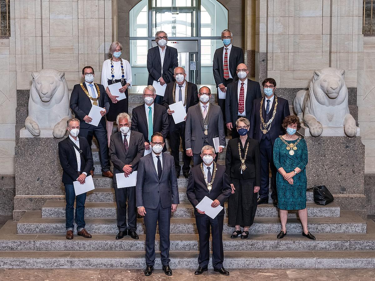 Das Foto zeigt auf den Stufen der von zwei Löwenstatuen eingerahmten Portaltreppe die Rektorinnen und Rektoren der 14 Hochschulen sowie die Dekane der beiden medizinsichen Fakultäten in Leipzig und Dresden mit dem Staatsmiminister der Mitte. Alle tragen FFP-Masken.
