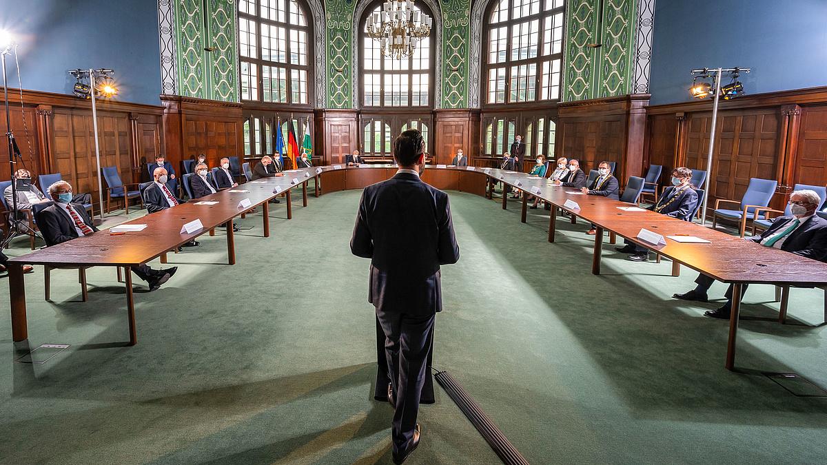Das Foto zeigt den großen Saal des Sächsichen Wissenschaftsmimisteriums in Dresden, die frühere Dreiköngisschule. An einer U-förmigen Tischaufstellung sitzen die Rektorinnen und Rektoren der Hochschulen. Zu ihnen spricht der Wissenschaftsminister, der an einem Rednerpult stehend von hinten zu sehen ist.