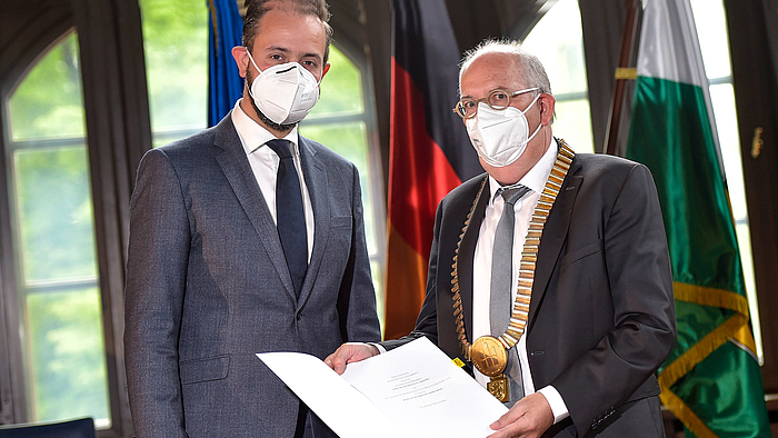 Das Foto zeigt zwei männliche Personen jeweils mit weißer FFP-Maske: links den Sächsischen Wissenschaftsminister Sebastian Gemkow, daneben den Mittweidaer Hochschulrektor Ludwig Hilmer. Dieser hält eine geöffnete Mappe mit der soeben unterzeichneten Vereinbarung zum Betrachtenden. Der Inhalt ist zu erkennen.