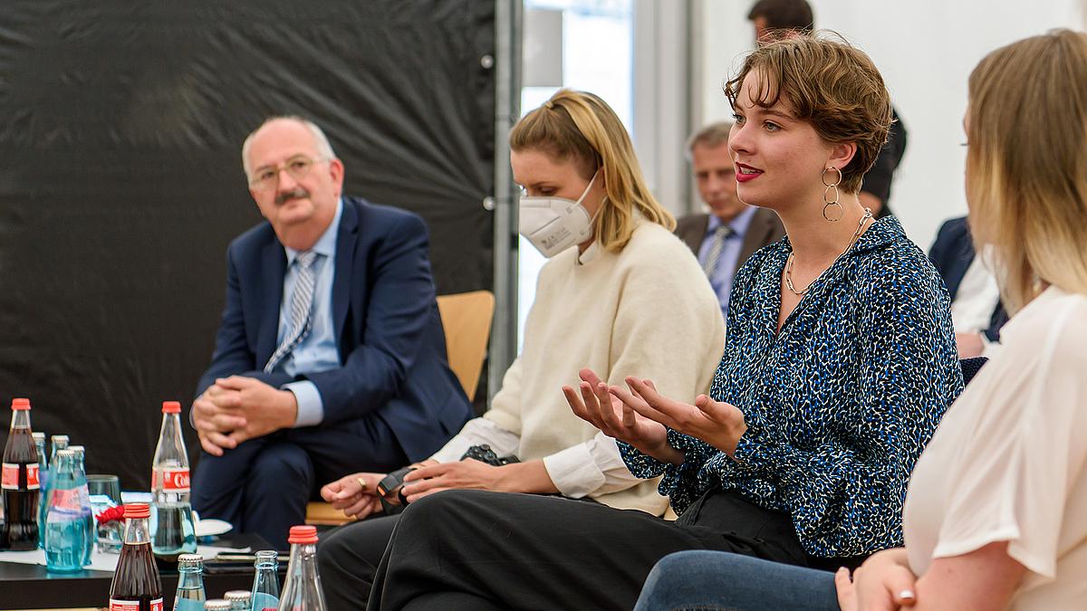 Eine Studentin spricht. Neben ihr sitzt eine Kommilitonin mit Maske, dahinter hört Rektor Ludwig Hilmer den Ausführungen zu.