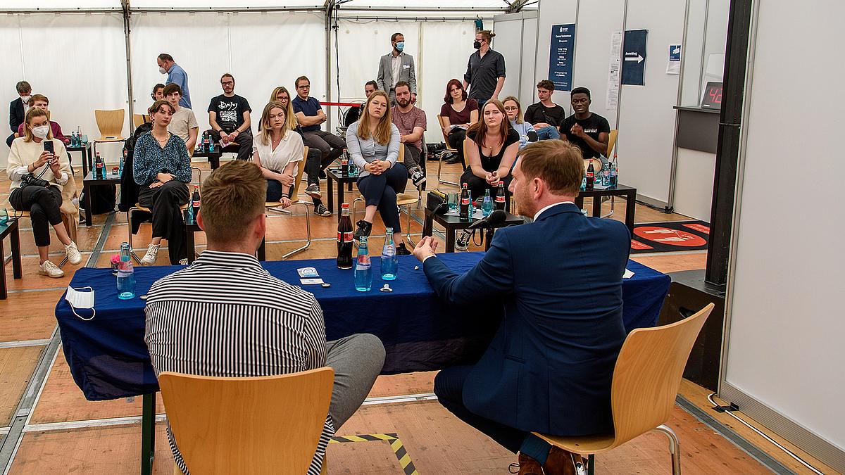 Sichtbar sind die Rücken von Michael Kretschmer und Gordon Guido Oswald. Im Hintergrund sitzen zahlreiche Studierende mit Abstand, die an der Diskussion teilnehmen.