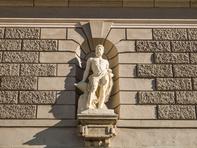 Eine von zwei Figuren an der Fassade zeigt Hephaistos, den griechischen Gott des Feuers und der Metallkünste; die andere ist Elektra.