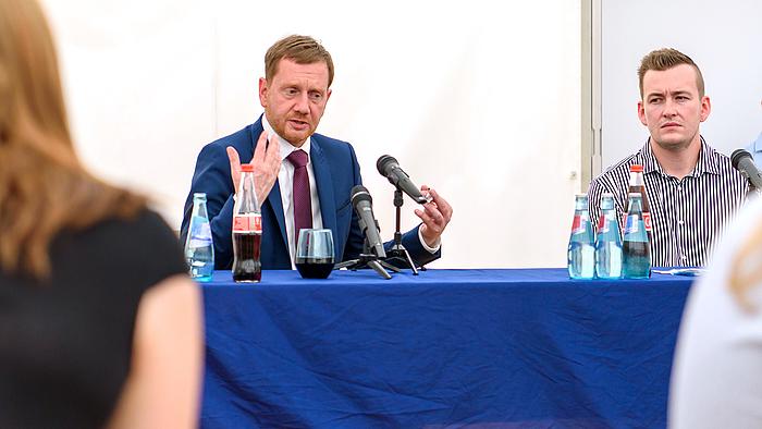 Ministerpräsident Michael Kretschmer spricht zu den Studierenden der Hochschule Mittweida. Rechts neben ihm sitzt Gordon Guido Oswald, Geschäftsführer des Studentenrats Mittweida.